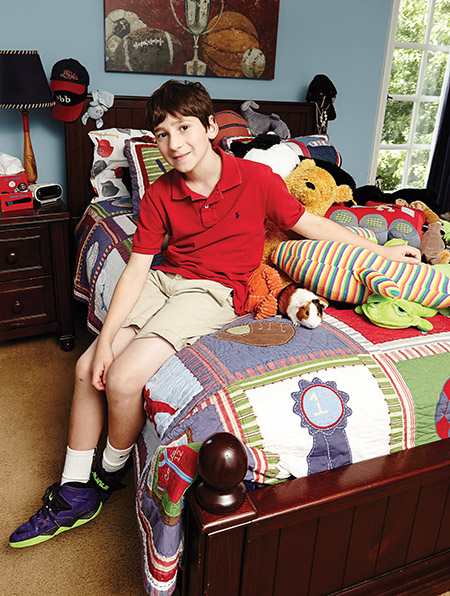 Ten-year-old Ian Yagoda in his bedroom, surrounded by some of the stuffed animals he's collected from hospital visits over the years. That's his guinea pig, Honey, next to him.
