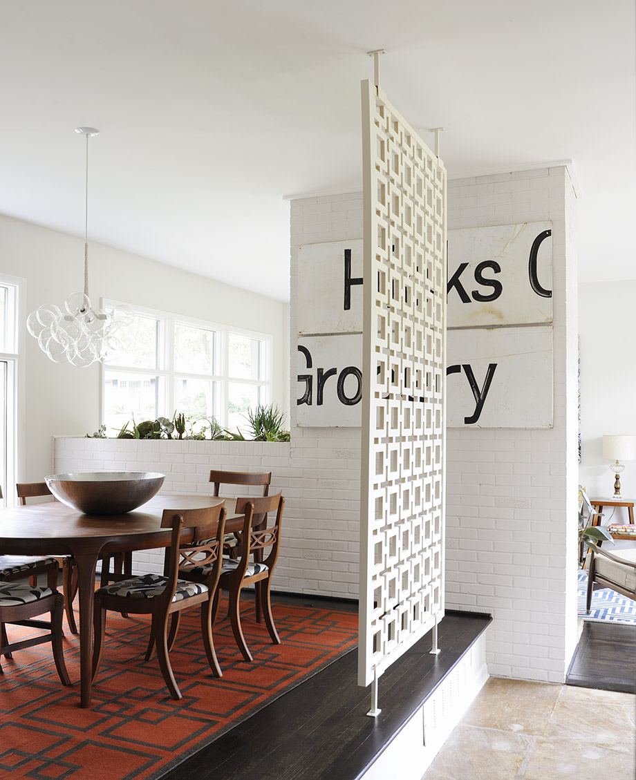 The dining room includes items old, like the Danish walnut table, and new, like the blown-glass bubble chandelier and a rug from West Elm. The Hicks Grocery sign (no relation) was salvaged from a local store.