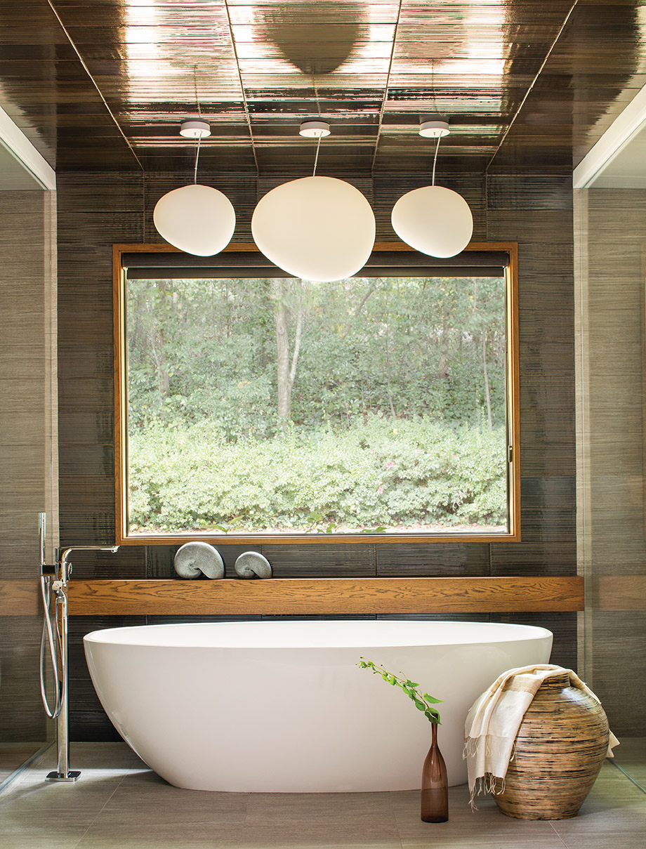 Polished stainless steel fixtures throughout the bathroom contrast nicely with more natural materials. Glossy tiles on the ceiling and wall further reflect sunlight throughout the room.