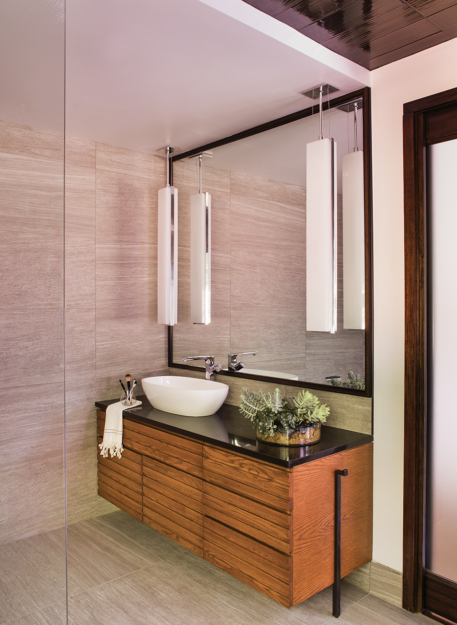 Pocket doors prevented the use of mounted sconces. The solution? Hanging pendant lights from the ceiling, which gives the look of lighting right on the mirror.