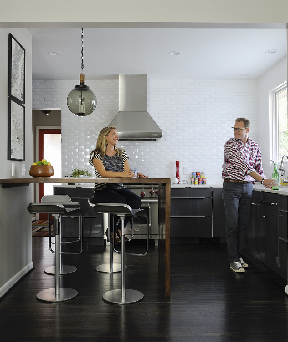 The Poors' Ikea kitchen is practical and chic, thanks to clean-lined walls (no upper cabinets) and a walnut waterfall-style bar table.