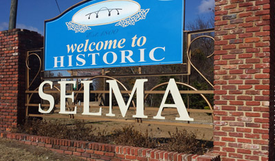 The welcome sign sits at the foot of the Edmund Pettus Bridge.