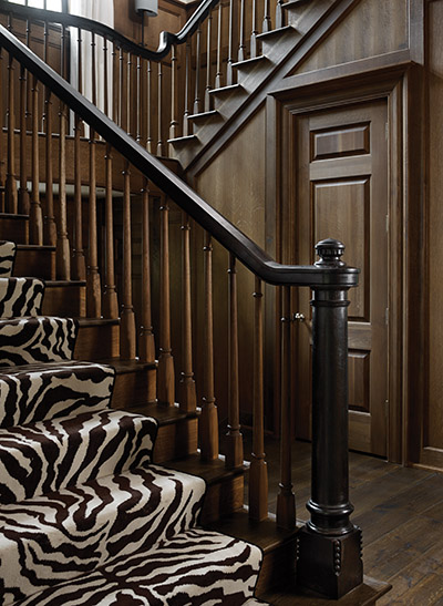 "The staircase's newel post, handrails, and pickets were all custom-designed and carved, then ebonized and fumed rather than painted. The silky finish comes from a heavy coat of Briwax. The flooring consists of 10-inch-wide oak planks in a custom stain. Neely insisted that each board be at least 10 feet long to imply old growth. Wide, short planks look like a ""checkerboard,"" he says."