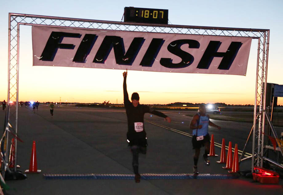 A runner proudly finishes The Mayor's Inaugural 5K on the 5th Runway
