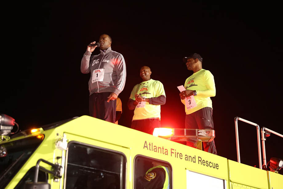 Mayor Kasim Reed addresses runners from atop an airport fire engine.