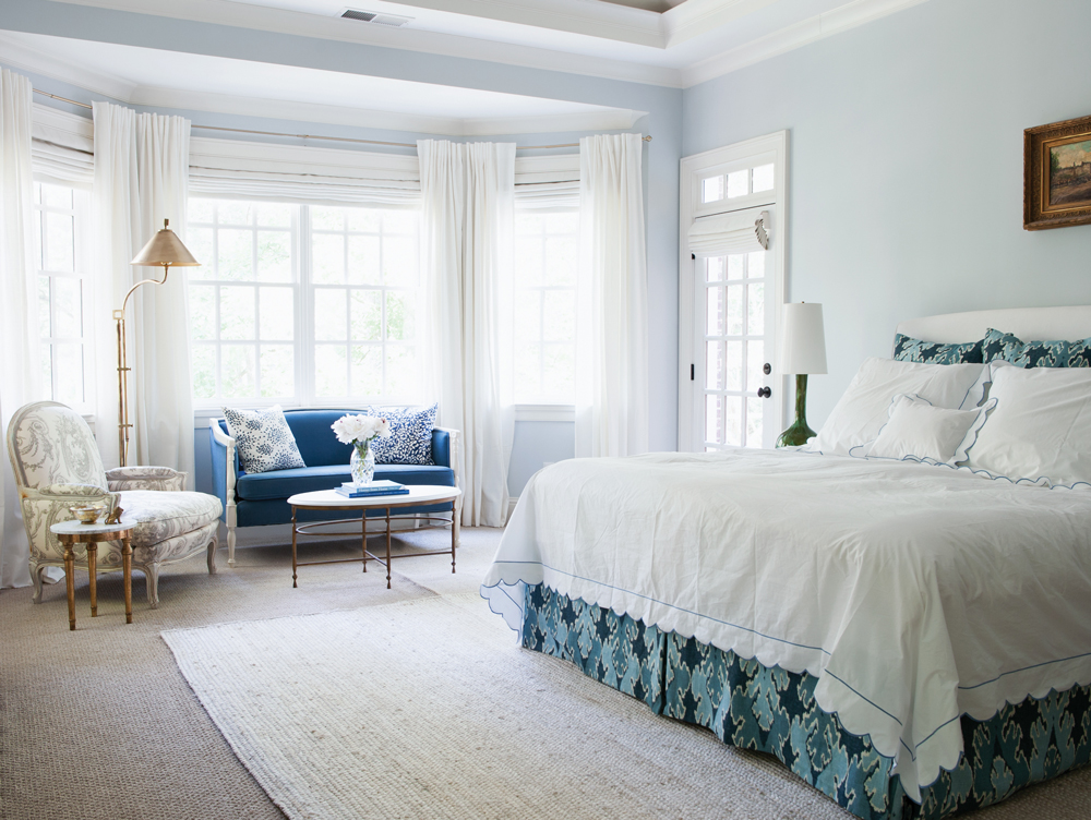"""""""I don't like a busy bedroom,"""" says the homeowner, whose master suite features a subdued blue-and-white scheme. Vintage bedside lamps are from Italy."""