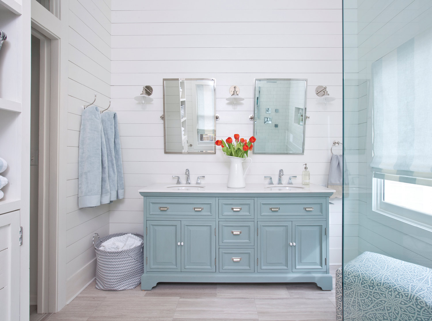 """The aqua color on the vanity and barn doors is very serene, while the white walls keep things fresh,"" says designer Lisa Gabrielson."
