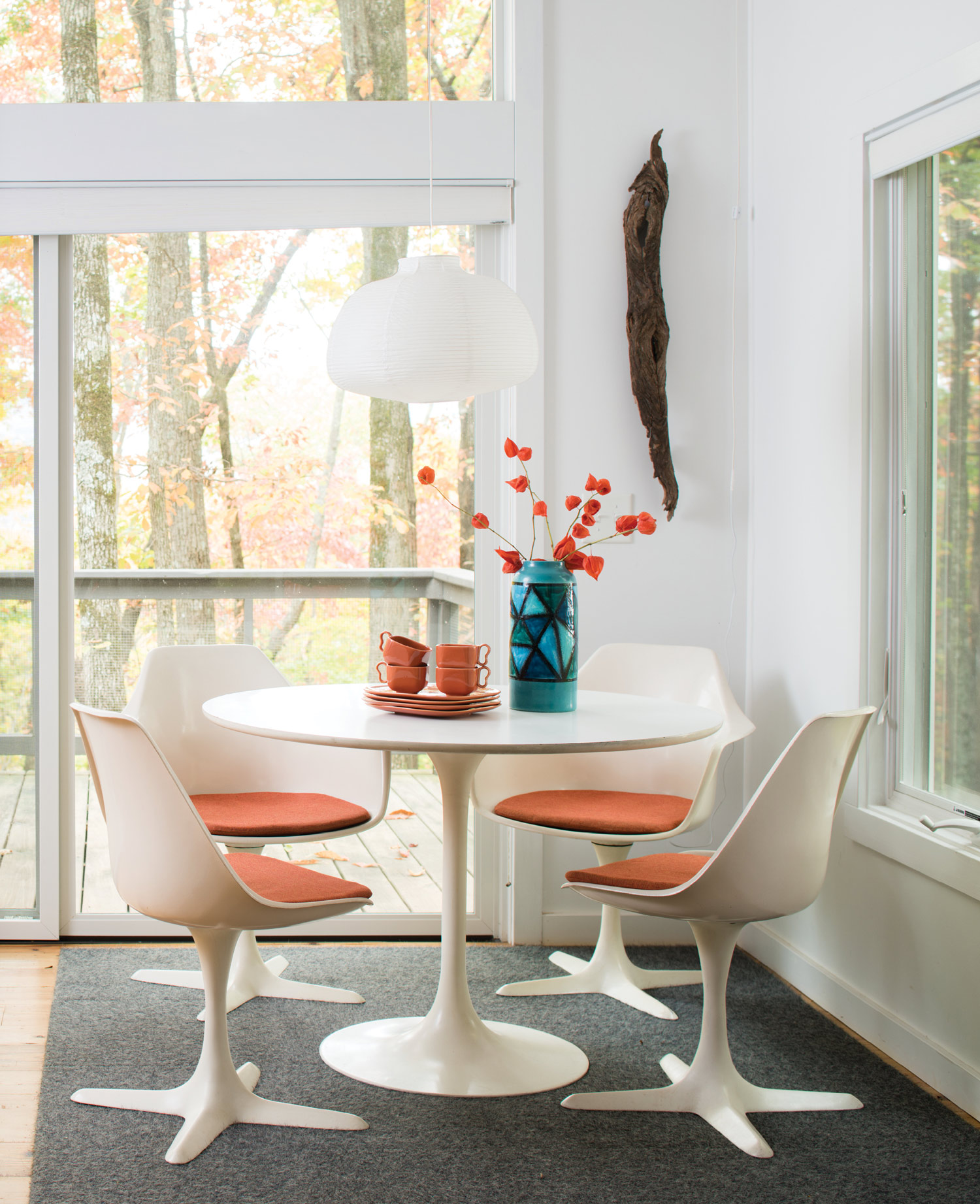 The 1940s Franciscan Metropolitan dishes and the new seat cushions on the vintage Burke dining set bring pops of orange to the dining room. The Noguchi-style pendant light is from Ikea. Interface carpet tiles protect the pine floor.