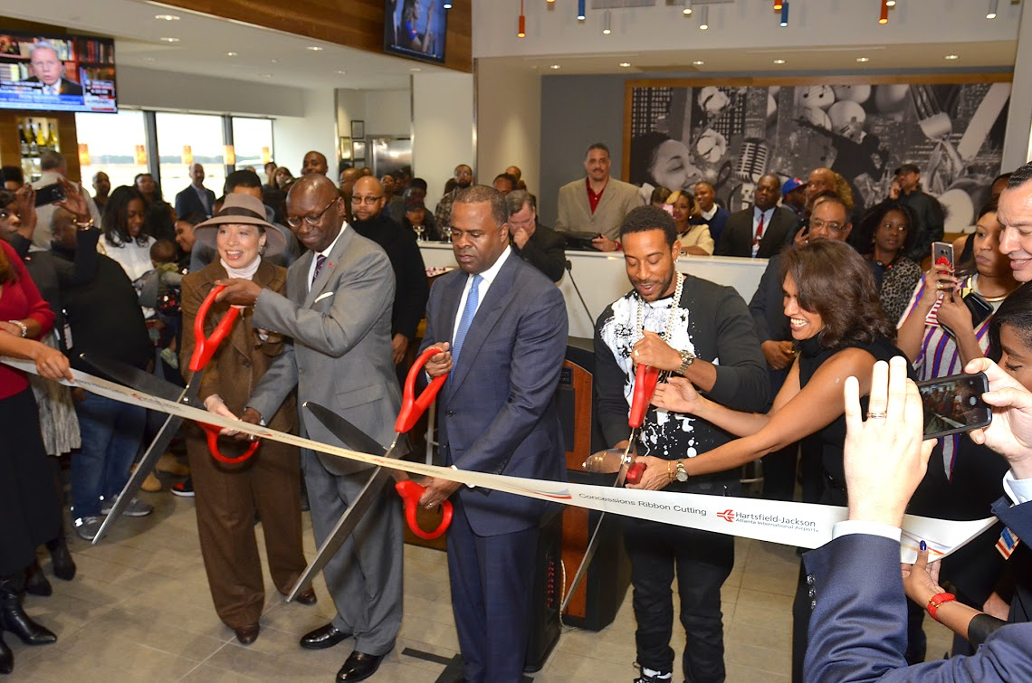 "Chris ""Ludacris"" Bridges cuts the ribbon, marking the opening of Chicken+Beer, alongside Atlanta Mayor Kasim Reed."