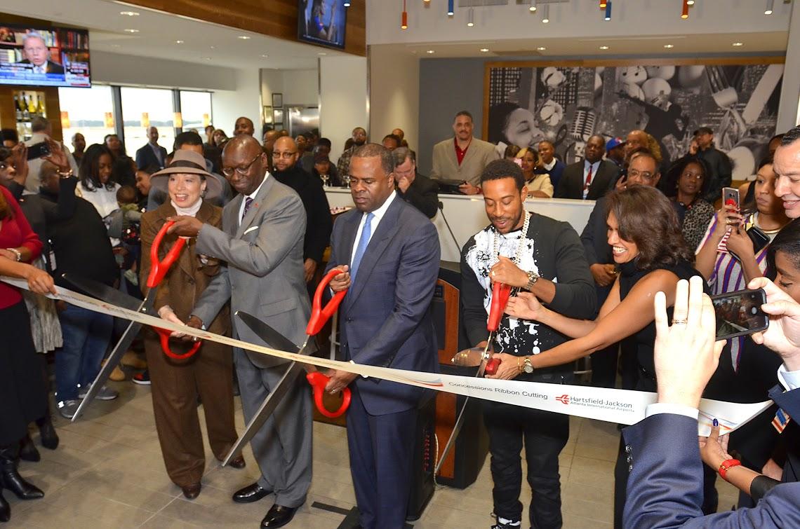 "Chris ""Ludacris"" Bridges cuts the ribbon, marking the opening of Chicken+Beer, alongside Atlanta Mayor Kasim Reed."