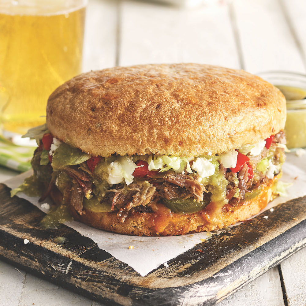 """Schlotsky's """"The Rancher"""" sandwich: hickory-smoked brisket and cheddar with roasted red peppers, pickled jalapeño, quest fresco, salsa verde, lettuce, and chipotle mayo."""