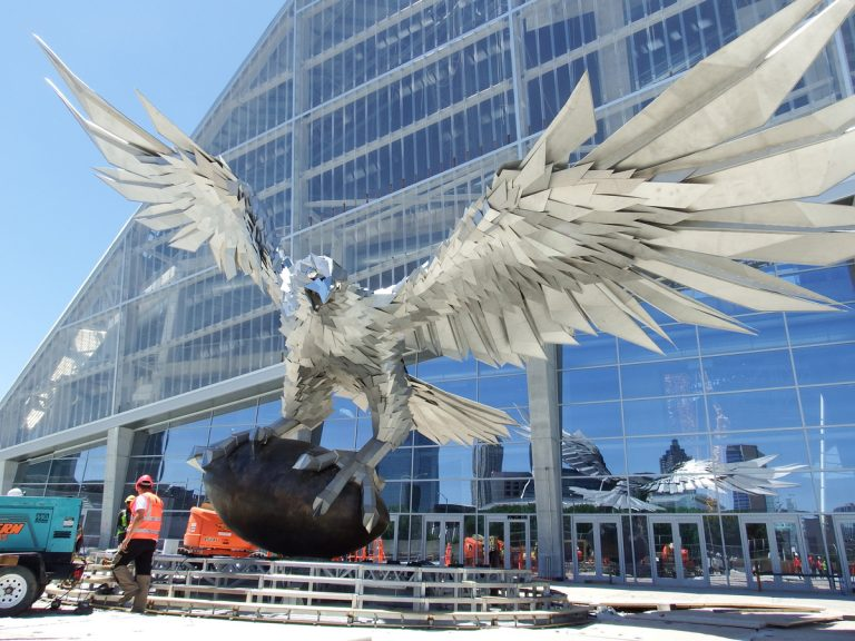 A giant stainless steel falcon is rising up in front of Mercedes-Benz Stadium