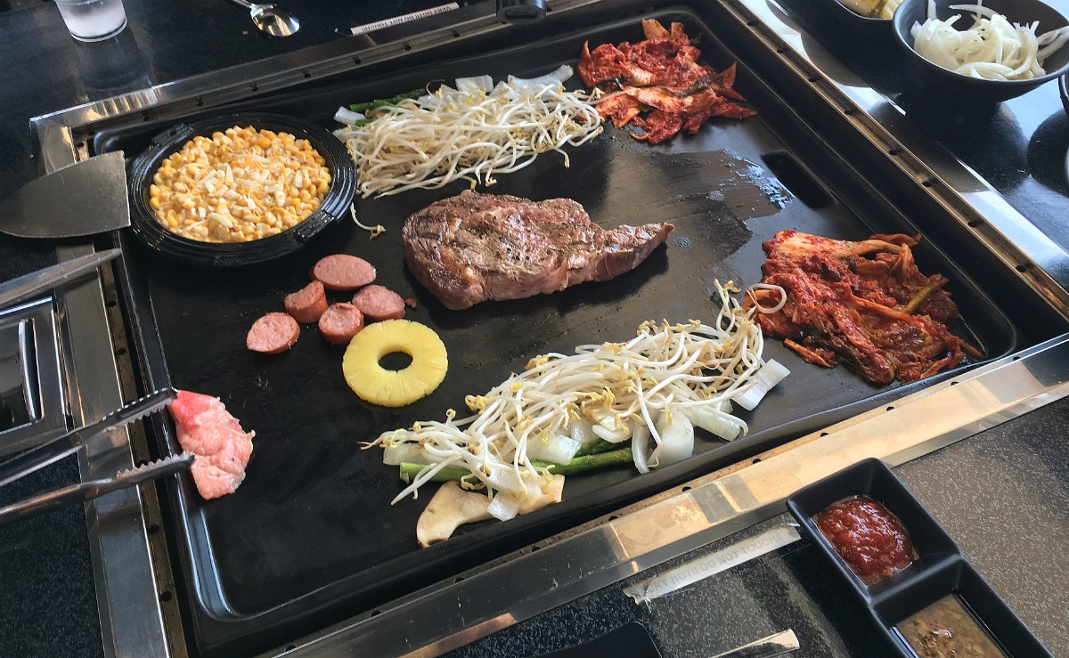 A Steak On The Grill Along With Kimchi Vegetables Cheesy Corn And More