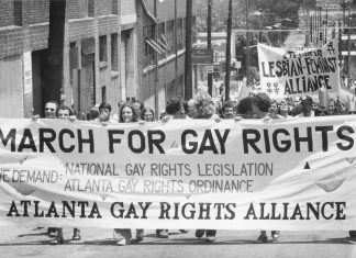 "Protesters march in downtown Atlanta holding a ""March for gay rights"" sign"
