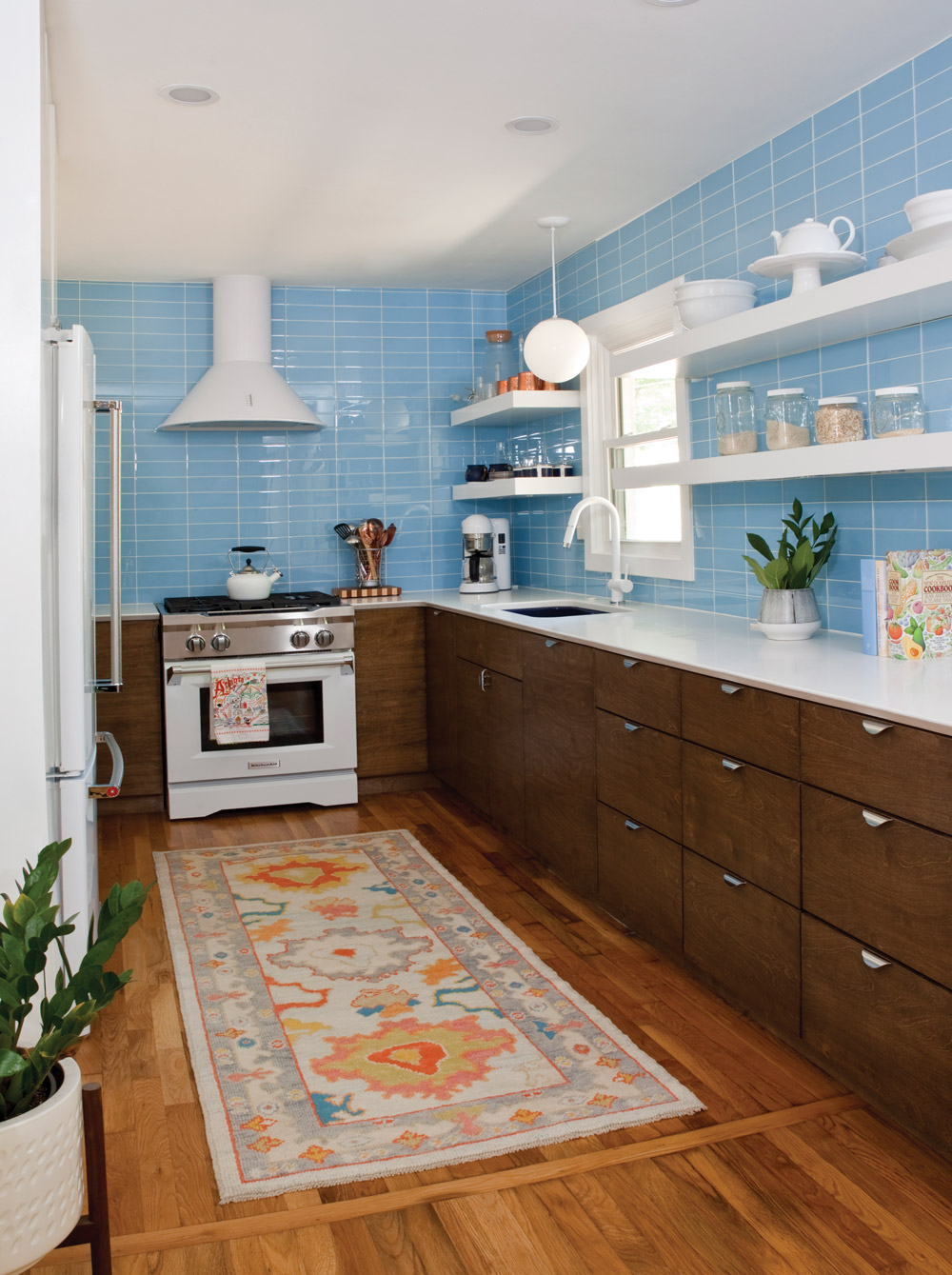 A quaint kitchen with blue tile, white countertops, and dark brown wood drawers