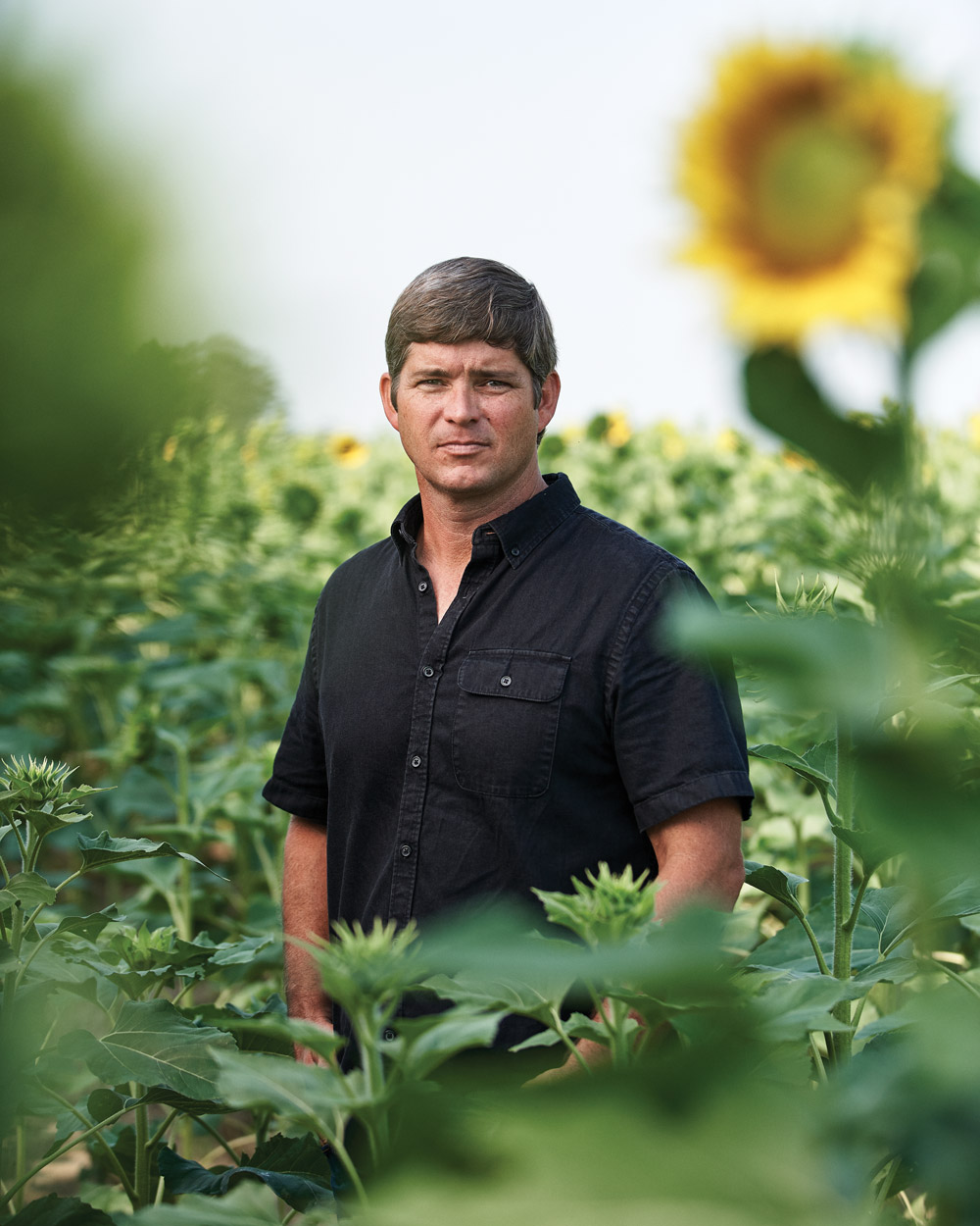 Clay Oliver standing in a field of flowers