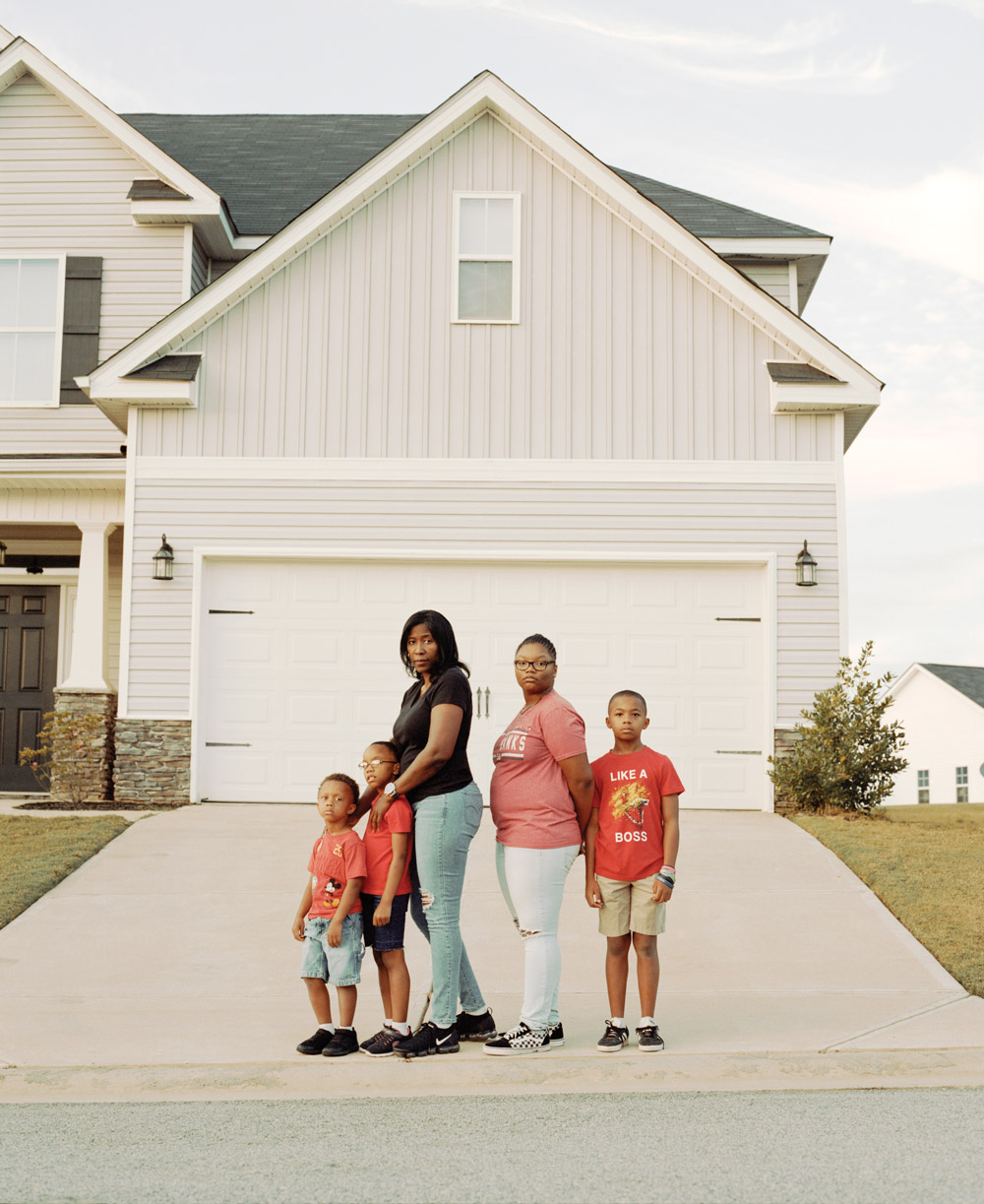 Demetress Williams standing outside her home with four of her foster children