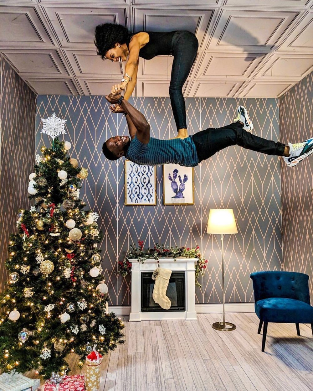 A couple poses in an upside down Christmas room