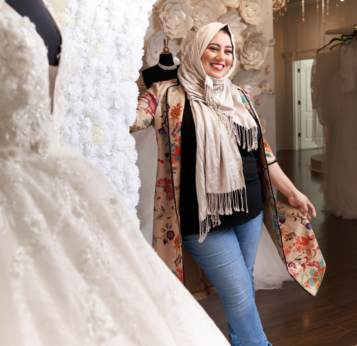 Rawan Asad standing next to a wedding gown