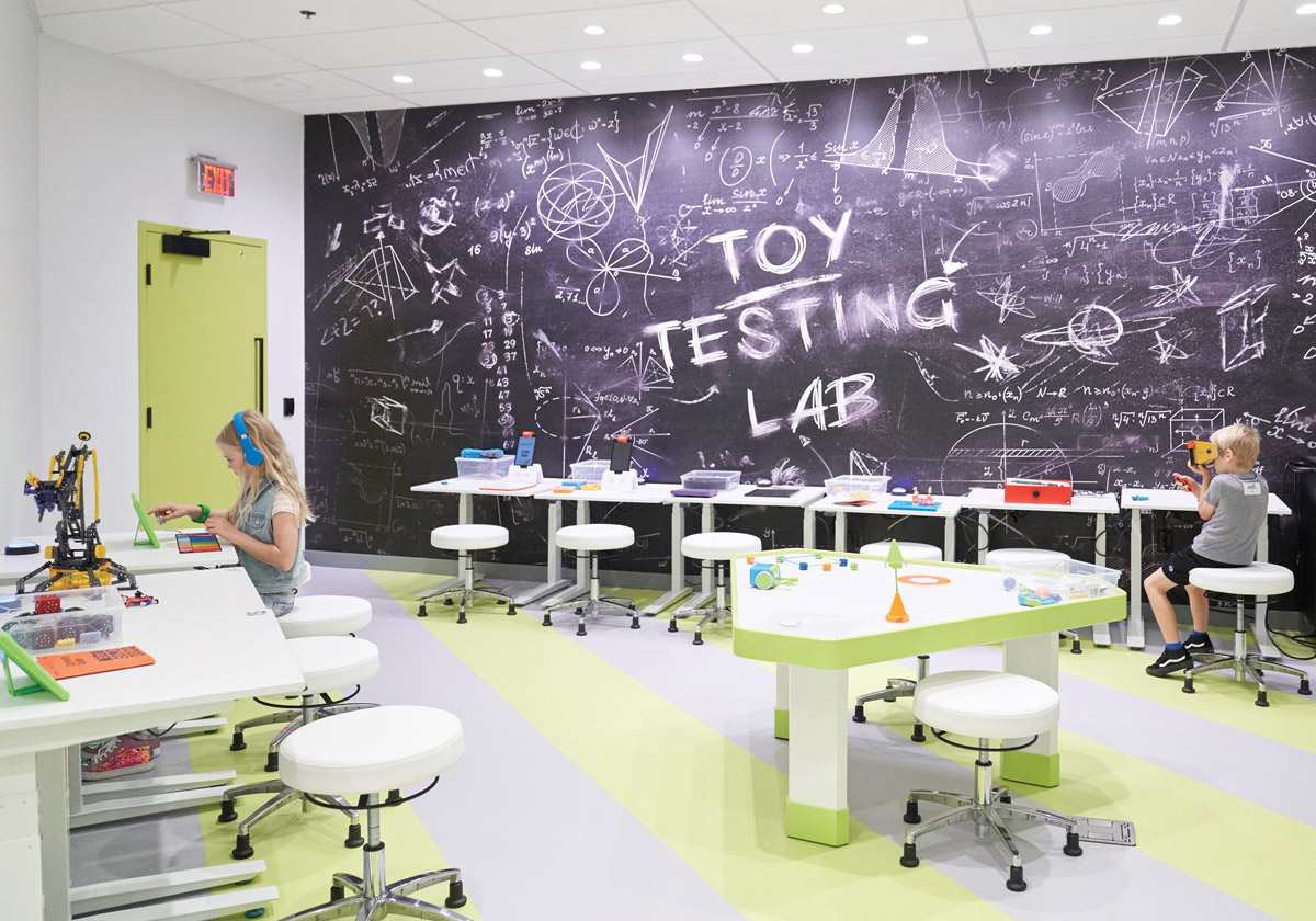 "Kids creating toys in a ""Toy Testing Lab"" with a giant chalkboard as one of the walls"
