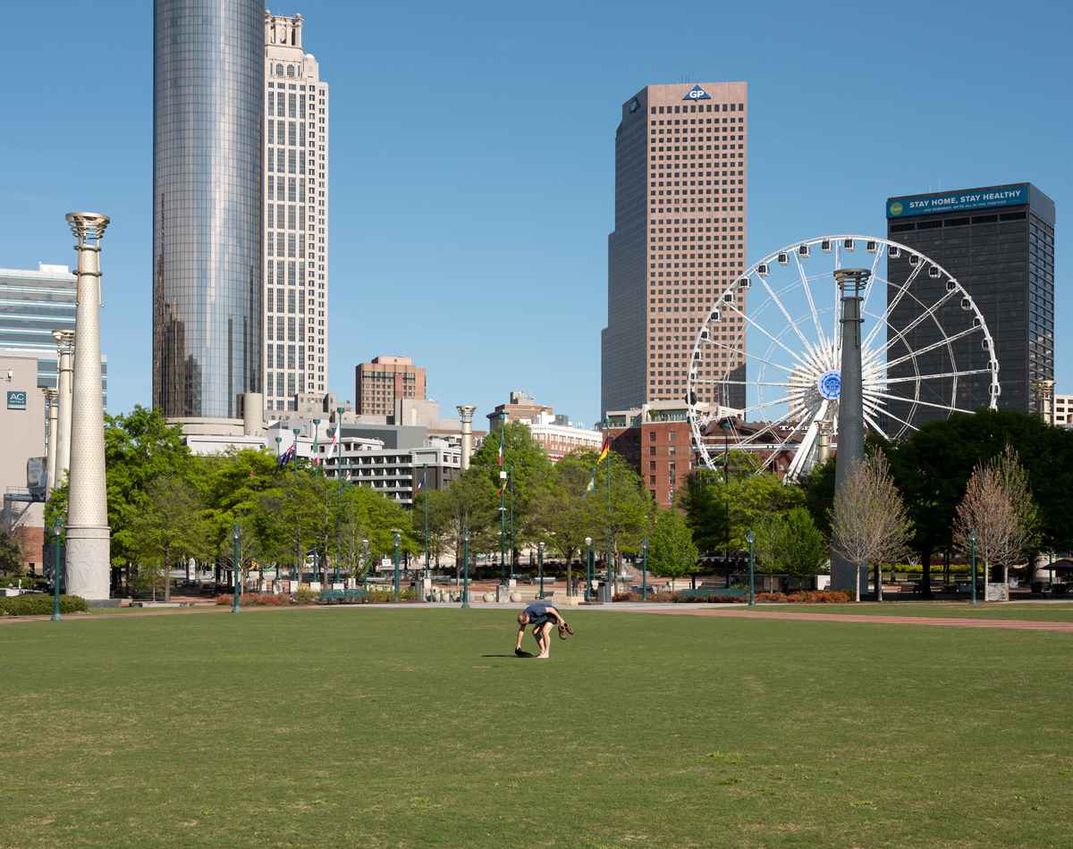 A man gathers his belongings in an empty Centennial Olympic Park on a Saturday afternoon.
