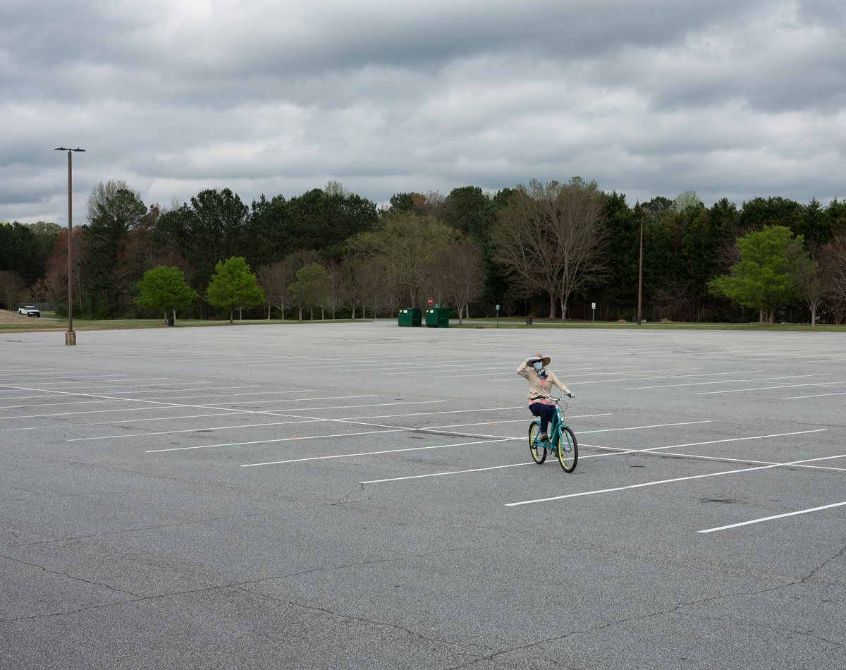 A woman rides her bike through an empty parking lot at Bishop Park in Marietta, GA.
