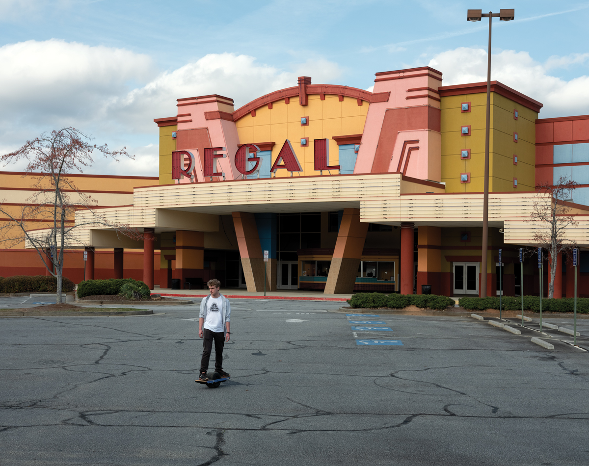 Someone skates through an empty parking lot at the Kennesaw Regal 13