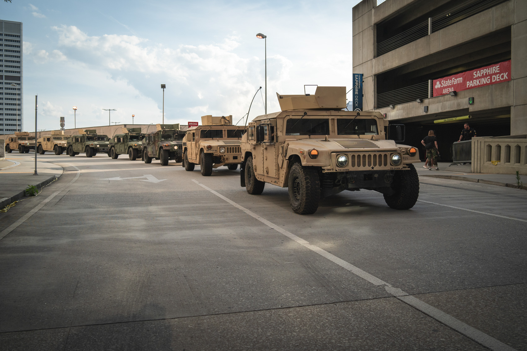 a line of Humvees traveling through dowtown
