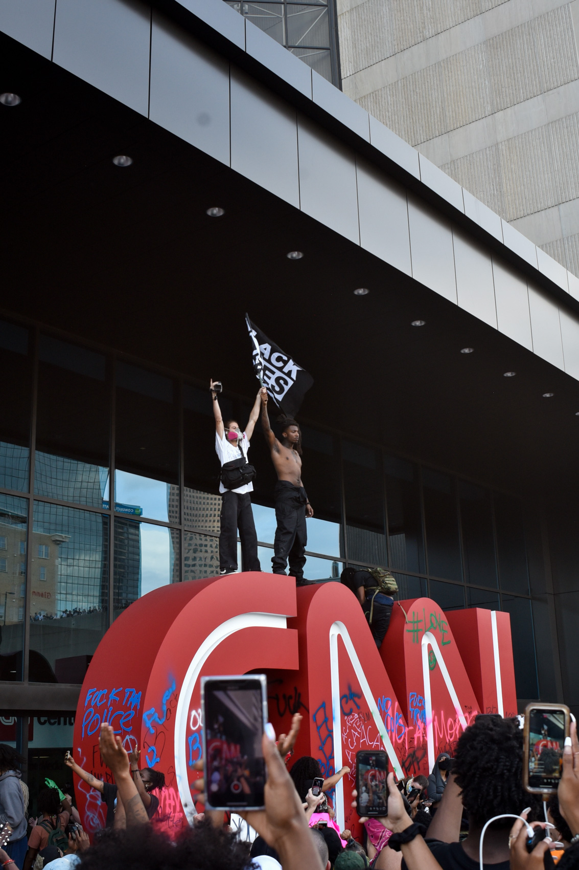 two protestors stand atop CNN sign holding