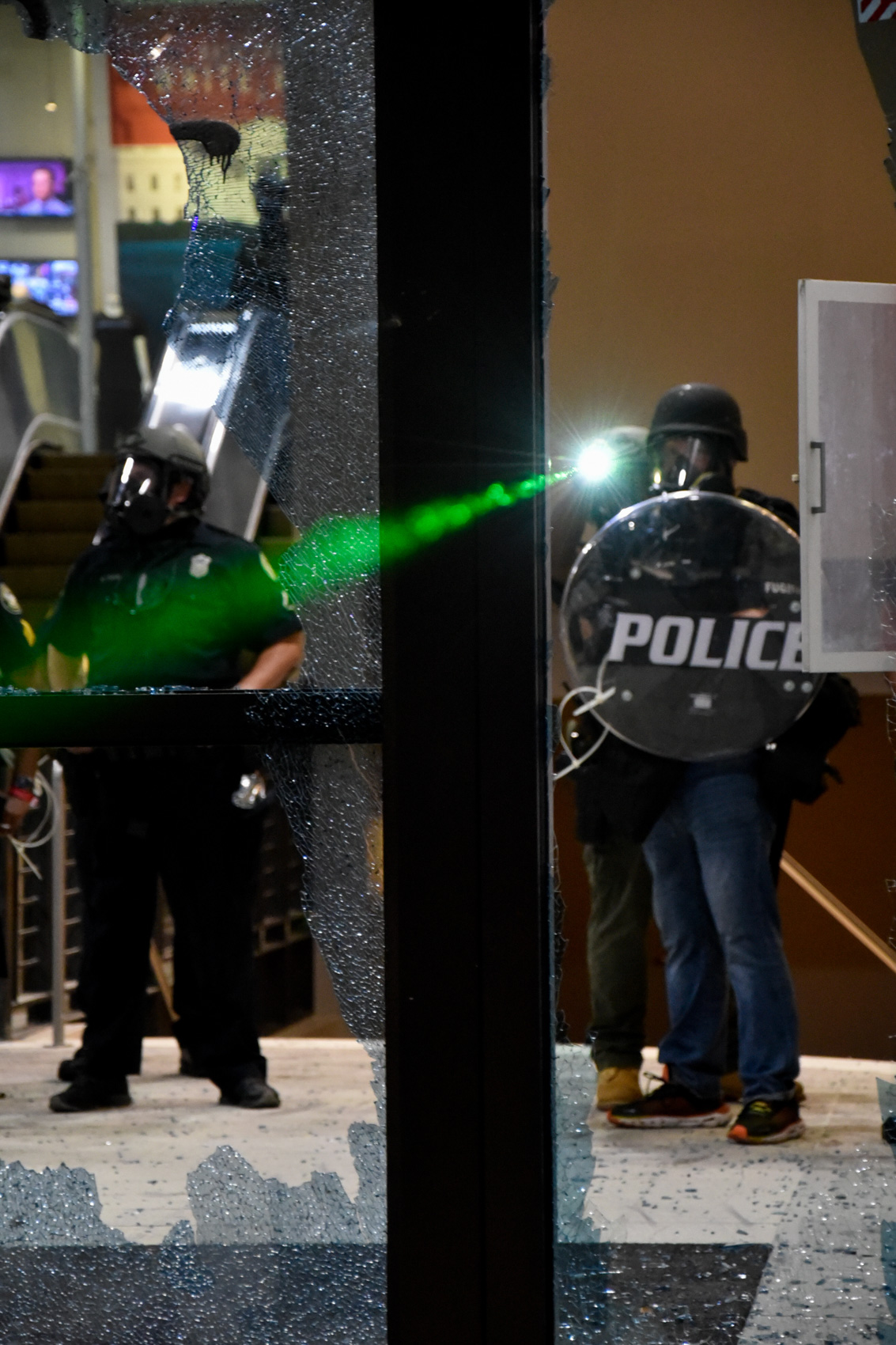 police officer holds up riot shield while another points a green laser