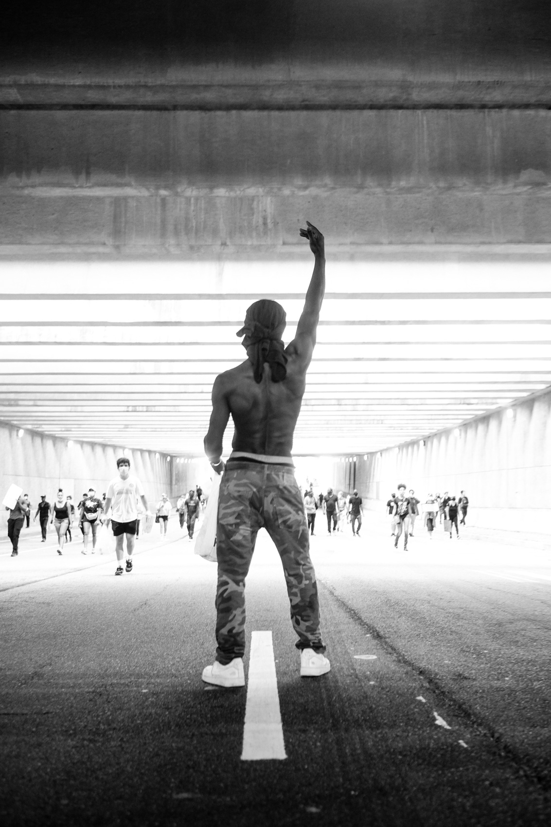 male protestor stands in tunnel with hand raised